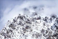 Mooie dramatische sneeuw de bergpieken van de Kaukasus in wolken Het toneel Landschap van de Winter stock fotografie