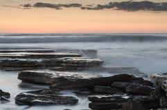Mooie dramatische Zonsondergang over een rotsachtige kust Royalty-vrije Stock Fotografie