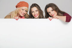 Mooie drie vrouwelijke vrienden met lege raad Royalty-vrije Stock Foto's