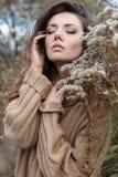 Mooie droevige leuke aantrekkelijke vrouw in een beige sweater wijd op een gebied van droog gras in de herfst koude donkere dag,  royalty-vrije stock foto's