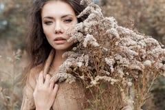 Mooie droevige leuke aantrekkelijke vrouw in een beige sweater wijd op een gebied van droog gras in de herfst koude donkere dag,  stock fotografie