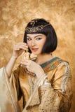 Mooie Egyptische vrouw zoals Cleopatra met parfumfles op gouden achtergrond Stock Afbeeldingen