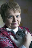 Mooie elegante bejaarde dame met een kat thuis Royalty-vrije Stock Afbeelding
