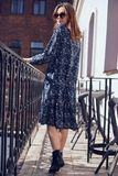 Mooie elegante donkerbruine vrouw die de zomer blauwe kleding op het balkon dragen Stock Foto