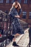 Mooie elegante donkerbruine vrouw die de zomer blauwe kleding op het balkon dragen Stock Foto's