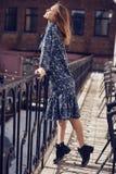 Mooie elegante donkerbruine vrouw die de zomer blauwe kleding op het balkon dragen Stock Afbeelding