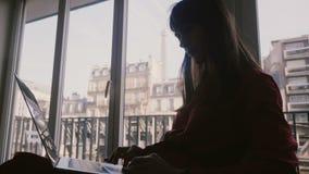 Mooie elegante jonge onderneemster die laptop met behulp van bij ruimtevenster met de Torenmening van Eiffel over zakenreis in Pa stock video