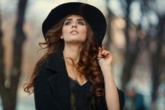 Mooie elegante vrouw in zwarte hoed openlucht De manier ziet eruit, euro Stock Foto