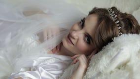 Mooie en mooie bruid in nachttoga op het bed Huwelijksochtend Vrij en hetverzorgde vrouw glimlachen Langzame Motie stock footage