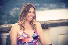 Mooie en charmante het glimlachen vrouwenzitting openlucht royalty-vrije stock foto