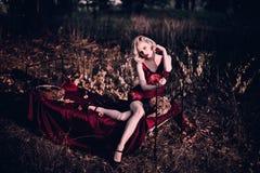 Mooie en elegante blondevrouw met rode lippen en haargolven die wijn het rode nachtjapon stellen op de retro bed in openlucht her Stock Foto