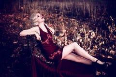 Mooie en elegante blondevrouw met rode lippen en haargolven die wijn het rode nachtjapon stellen op de retro bed in openlucht her Royalty-vrije Stock Afbeeldingen