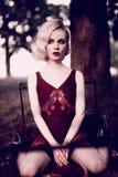 Mooie en elegante blondevrouw met rode lippen en haargolven die wijn het rode nachtjapon stellen op de retro bed in openlucht her Royalty-vrije Stock Afbeelding