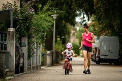 Mooie en gelukkige jonge moeder die haar leuke dochter onderwijzen om een fiets te berijden Allebei die, de Zomerstraat op achter stock foto