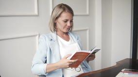 Mooie en jonge succesvolle bedrijfsvrouw die met boek in een koffie glimlachen, die het boek lezen Blondewijfje in blauw stock videobeelden