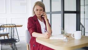 Mooie en jonge succesvolle bedrijfsvrouw met mobiele telefoon en blocnote in een koffie, die als freelancer werken Blonde stock footage