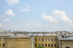 Mooie en krachtige wolken tegen de blauwe hemel en de daken van de stad stock afbeelding