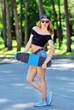Mooie en manier het jonge vrouw stellen met een skateboard royalty-vrije stock foto