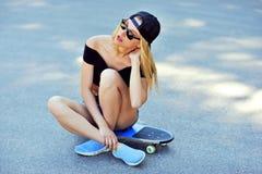 Mooie en manier het jonge vrouw stellen met een skateboard royalty-vrije stock afbeeldingen