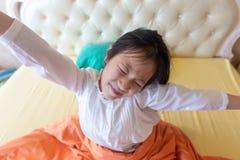 Mooie en meisjesontwaken in haar bed, Aziatisch meisje die, gezond, levensstijlconcept uitrekken glimlachen zich royalty-vrije stock afbeeldingen
