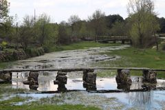 Mooie en oude zeer oude steenbrug die ons toestaat om de rivier over te gaan royalty-vrije stock foto