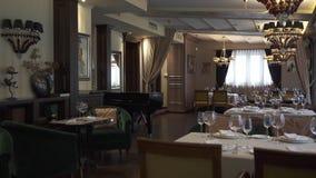 Mooie en rijk gediende lijsten in het restaurant Een comfortabele verfraaide ruimte Luxeontvangst modieuze glazen, platen stock videobeelden