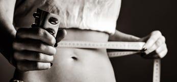Mooie en sterke vrouwen` s abs met meter en pillen stock fotografie