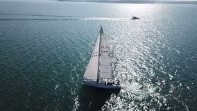 Mooie epische hommel luchtlengte op warme zonnige dag bij blauwe open oceaan op zee, wit professioneel jacht tijdens het rennen stock video