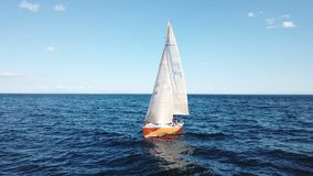 Mooie epische hommel luchtlengte op warme zonnige dag bij blauwe open oceaan op zee, wit professioneel jacht tijdens het rennen stock footage