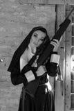 Mooie ernstige boze non die een geweer, kanon houden Beeld van een meisje met een kanon Het gevaarlijke kanon van de nonholding royalty-vrije stock afbeelding