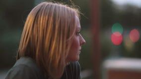 Mooie ernstige jonge vrouwenzitting in een koffie Close-up, vage lichten, stedelijke straat, zijaanzicht stock video