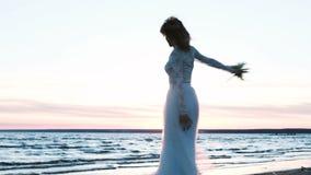 Mooie Europese bruid met een origineel boeket van het met de hand gemaakte spinnen op het overzees bij zonsondergang Gelukkige vr stock video