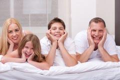 Mooie familie die bij bed het glimlachen ligt Stock Afbeeldingen