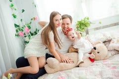 Mooie familie die en, die bij camera glimlachen lachen stellen royalty-vrije stock afbeeldingen