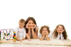 Mooie familie die op een rij op tapijt leggen Stock Afbeelding