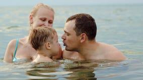 Mooie familie met kind het baden in overzees stock video