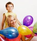 Mooie familie met kleurenballons op witte achtergrond, blonde vrouw met weinig jongen op verjaardagspartij Royalty-vrije Stock Foto