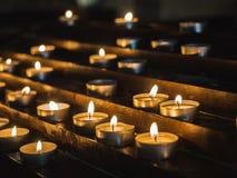 Mooie, feestelijke kaarsen in de duisternis van de oude Kerk stock foto's