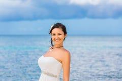 Mooie fiancee in de witte tribune van de huwelijkskleding op kustoverzees wed Stock Fotografie