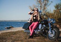 Mooie fietservrouw met motorfiets op het strand royalty-vrije stock afbeelding