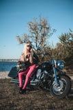 Mooie fietservrouw met motorfiets op het strand stock afbeelding