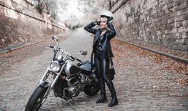 Mooie fietservrouw openlucht met motorfiets royalty-vrije stock fotografie