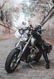 Mooie fietservrouw openlucht met motorfiets royalty-vrije stock foto