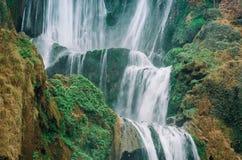 Mooie foto van Ouzoud-waterval in Marokko met zacht stromend water en grote gekleurde rotsen Groene wilde wildernissen  royalty-vrije stock fotografie
