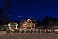 Mooie foto van plattelandshuisje met Kerstmislichten in Zweden Scandinavië Stock Fotografie