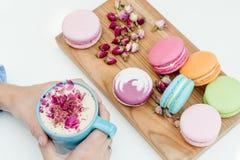 Mooie Franse macarons op het bureau Vrouwenhanden die een blauwe kop van cappuccino met rozenbloemblaadjes houden Royalty-vrije Stock Fotografie