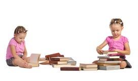 Mooie geïsoleerde tweelingenmeisjes met stapel van boeken Stock Foto's