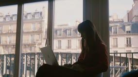 Mooie geconcentreerde freelance jonge onderneemster in kleding die laptop zitting gebruiken bij groot flatvenster in de zomer Par stock videobeelden