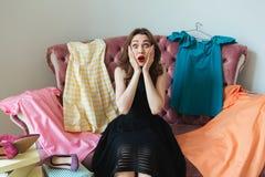 Mooie gefrustreerde vrouw in kledingszitting op een bank Stock Afbeelding