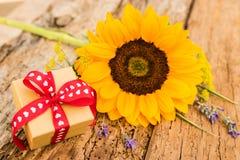 Mooie gele zonnebloem met kleine giftdoos met hartenlint op uitstekende houten achtergrond voor Valentijnskaartendag of Moedersda Stock Foto's